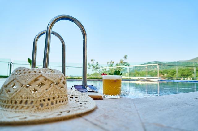 klobouk, brýle a sklenice piva u bazénu